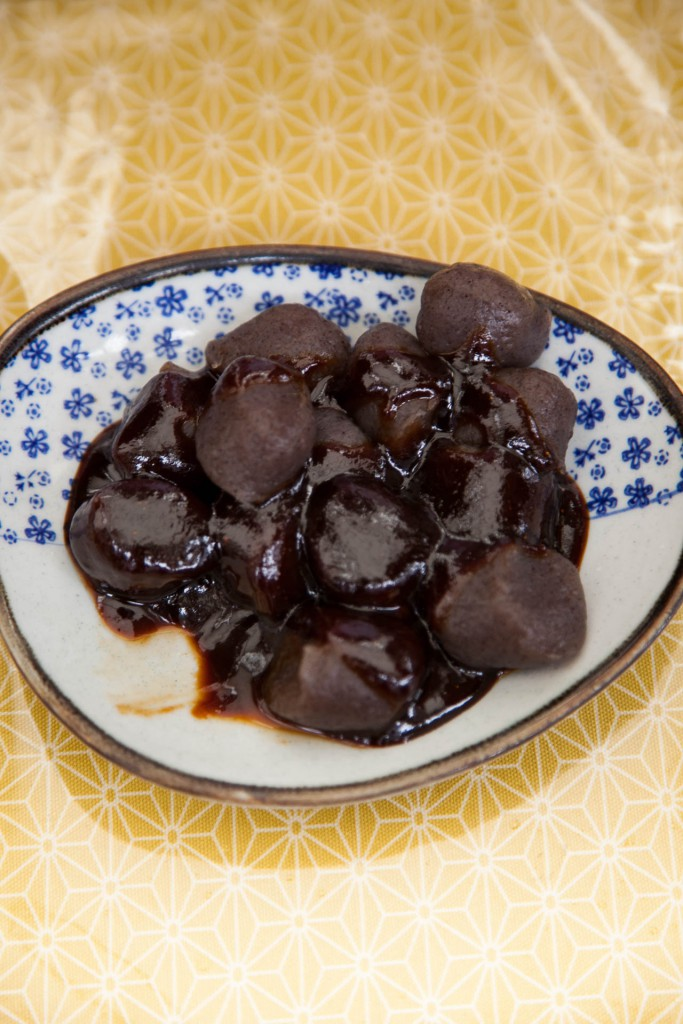 """One way of enjoying hatcho miso, is mixed together with pieces of konnyaku. Seen here the miso is rich dark colour. This is typical of hatcho miso. The main element that decides the colour is """"Maillard Chemistry"""". This is a non-enzymatic browning reaction and happens when sugar molecules and amino acids are heated together. The degree of Maillard Chemistry depends on ingredients and the method of production, but generally the more the reaction happens, the more brown miso becomes. Therefore, mame-miso is usually a dark colour and needs longer time to ferment. Hatcho Miso turns brownish as a result of steamed soybeans. Apparently, steaming soybeans is much more nutritional than boiling them."""
