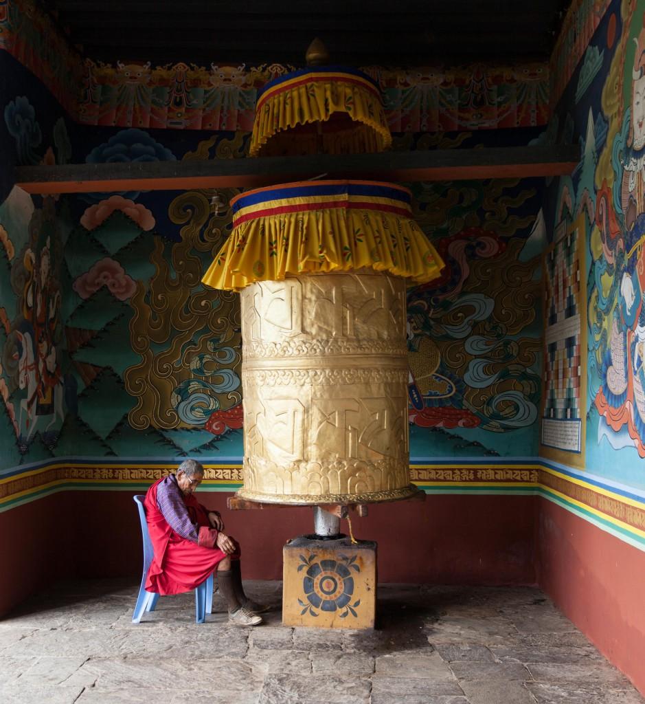 An elderly man at the large prayer wheel in Punakha Dzong.